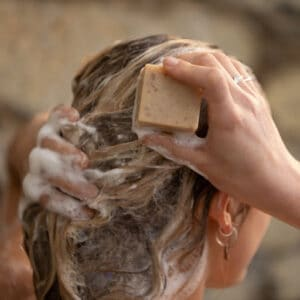 Gently rub your solid shampoo bar onto your hair directly.